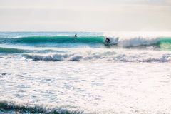 Paseo de la persona que practica surf en onda azul ideal Invierno que practica surf en el océano Foto de archivo libre de regalías