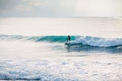 Paseo de la persona que practica surf en onda del barril El practicar surf en el océano Fotos de archivo