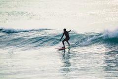 Paseo de la persona que practica surf en onda Invierno que practica surf en el océano Fotos de archivo