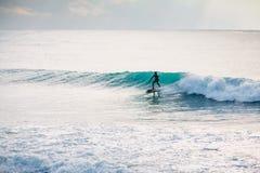 Paseo de la persona que practica surf en onda Invierno que practica surf en el océano Imagenes de archivo