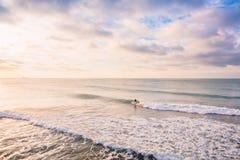 Paseo de la persona que practica surf en onda perfecta del barril Paisaje con colores de la salida del sol Imagen de archivo