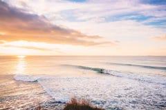 Paseo de la persona que practica surf en onda perfecta del barril Paisaje con las ondas y los colores de la salida del sol Fotos de archivo