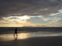 Paseo de la playa de la puesta del sol Foto de archivo libre de regalías