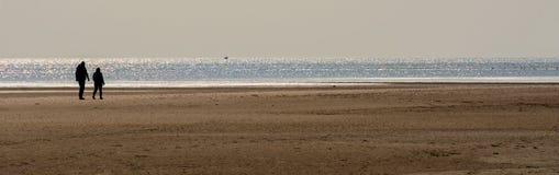 Paseo de la tarde en una playa Imagenes de archivo