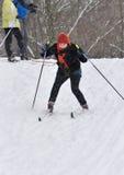 Paseo de los esquiadores de una colina fotos de archivo