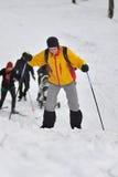 Paseo de los esquiadores en la madera de la nieve foto de archivo libre de regalías
