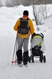 Paseo de los esquiadores en la madera de la nieve imágenes de archivo libres de regalías