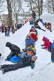 Paseo de los niños con una diapositiva de la nieve Imagen de archivo libre de regalías
