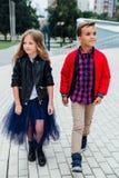 Paseo de los niños de los modelos de moda las escaleras de las calles de la ciudad Un muchacho y una muchacha, una falda azul Foto de archivo libre de regalías