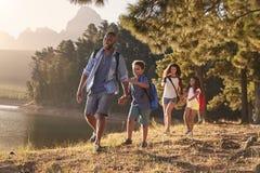 Paseo de los niños por el lago con los padres en la familia que camina aventura fotografía de archivo