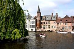 Paseo de los turistas a través en los canales Brujas. Fotografía de archivo libre de regalías