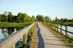 Paseo de madera de la gente de la falta de definición del lago de las verjas de la pasarela Fotos de archivo libres de regalías