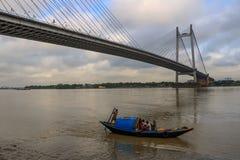 Paseo de madera del barco del país en el río el Ganges en un día nublado con el Vidyasagar Setu (puente) en el contexto Imágenes de archivo libres de regalías