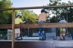 Paseo de tres adolescentes en la vespa del retroceso por el skatepark Fotografía de archivo