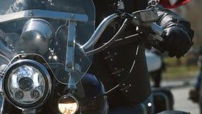 Paseo del grupo de muchos motoristas del subcultivo en la pista en un día de verano soleado en las motocicletas de encargo, una a