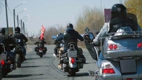 Paseo del grupo de muchos motoristas del subcultivo en la pista en un día de verano soleado en las motocicletas de encargo, una a metrajes
