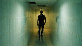Paseo del hombre abajo de un pasillo almacen de metraje de vídeo