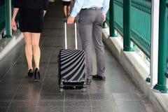 Paseo del hombre de negocios y de la empresaria así como el equipaje negro Fotografía de archivo