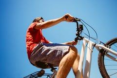 Paseo del hombre joven una bicicleta de debajo tiro imagen de archivo