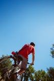 Paseo del hombre joven una bicicleta de debajo tiro trasero foto de archivo