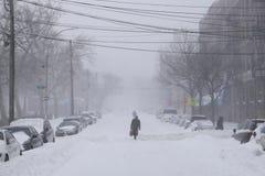 Paseo del hombre a lo largo de la calle nevada Imágenes de archivo libres de regalías