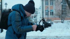 Paseo del operador de la cámara con el estabilizador electrónico en invierno almacen de metraje de vídeo