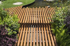 Paseo del tablero de madera en patio del jardín a lo largo del lado con una charca Imagen de archivo libre de regalías