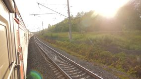 Paseo del tren de coches de ferrocarril en los carriles cerca del ferrocarril del bosque afuera El tren con los carros se mueve a almacen de metraje de vídeo