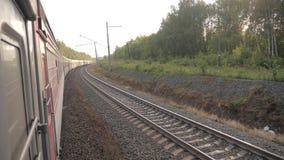 Paseo del tren de coches de ferrocarril en los carriles cerca del ferrocarril del bosque afuera vídeo de la cámara lenta El tren  almacen de metraje de vídeo