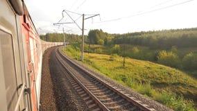 Paseo del tren de coches de ferrocarril en los carriles cerca del ferrocarril del bosque afuera vídeo de la cámara lenta El tren  metrajes