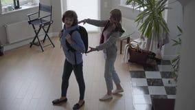 Paseo delgado de la mujer dentro de la casa hermosa con la mochila cómoda en la parte posterior y la mujer hermosa rubia encontra almacen de metraje de vídeo