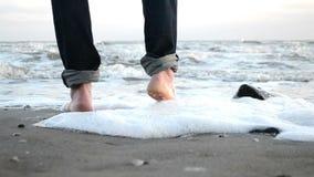 Paseo descalzo a lo largo de la orilla arenosa del mar del invierno almacen de video