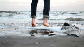 Paseo descalzo a lo largo de la orilla arenosa del mar del invierno almacen de metraje de vídeo
