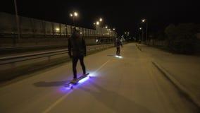 Paseo eléctrico de Longboard en ciudad de la noche con llevado y motores metrajes