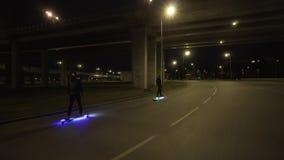 Paseo eléctrico de Longboard en ciudad de la noche con llevado y motores almacen de video