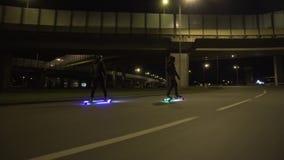 Paseo eléctrico de Longboard en ciudad de la noche con llevado y motores almacen de metraje de vídeo