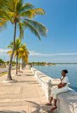Paseo el Prado embankment with local woman sitting Stock Image