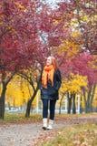 Paseo en el sendero en parque de la ciudad, temporada de otoño de la muchacha Foto de archivo