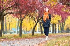 Paseo en el sendero en parque de la ciudad, temporada de otoño de la muchacha Imagen de archivo libre de regalías