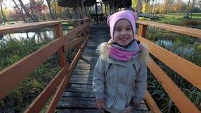 Paseo feliz de la muchacha del niño en el puente de madera en otoño Corriente del río en fondo almacen de video