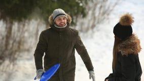 Paseo feliz de los pares en bosque de la nieve ellos que se vistieron en ropa del invierno almacen de metraje de vídeo