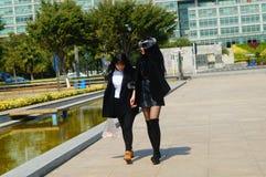 Paseo femenino de los turistas a través del cuadrado de ciudad Imágenes de archivo libres de regalías