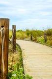 Paseo marítimo de madera en las dunas que llevan a la playa arenosa, el PA Imágenes de archivo libres de regalías