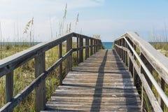 Paseo marítimo de madera rústico de la playa a través de las dunas de arena Imágenes de archivo libres de regalías