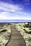 Paseo marítimo sobre las dunas de arena con el cielo azul Imagenes de archivo