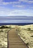 Paseo marítimo sobre las dunas de arena con el cielo azul y las nubes Fotografía de archivo