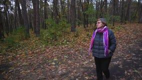 Paseo mayor de la mujer en el bosque del otoño y mirada en el cielo almacen de metraje de vídeo