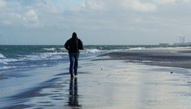 Paseo mojado y frío en la playa Fotografía de archivo