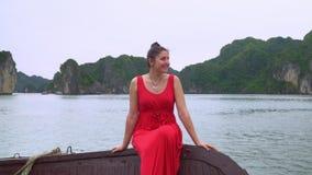 Paseo por el barco La mujer sonriente por el barco Vietnam Morenita hermosa en un vestido rojo que flota en un barco Un viaje almacen de video