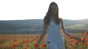 Paseo sensual joven de la muchacha entre la flor de la amapola en campo almacen de video